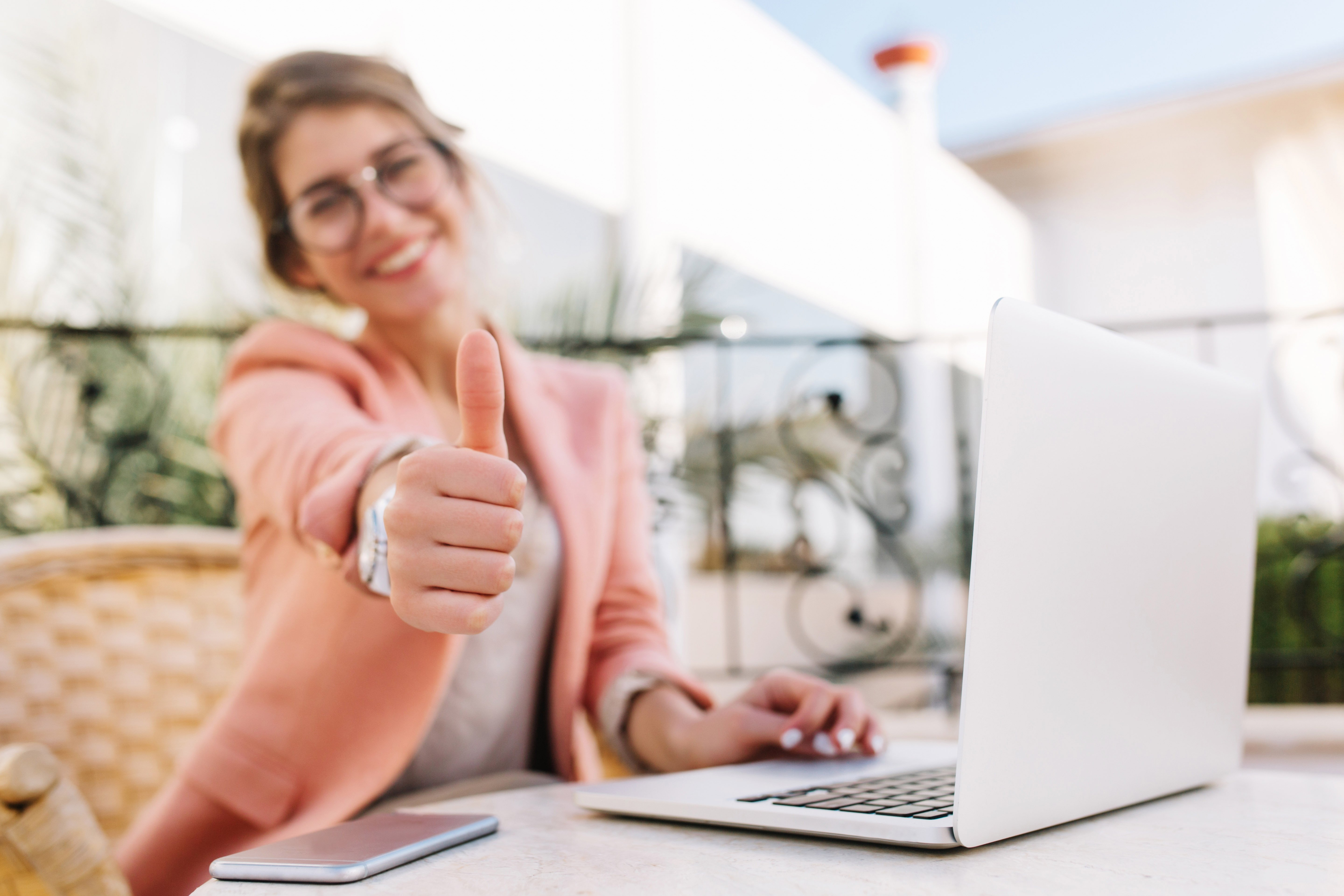 woman sitting in front of her computer giving a thumbs up