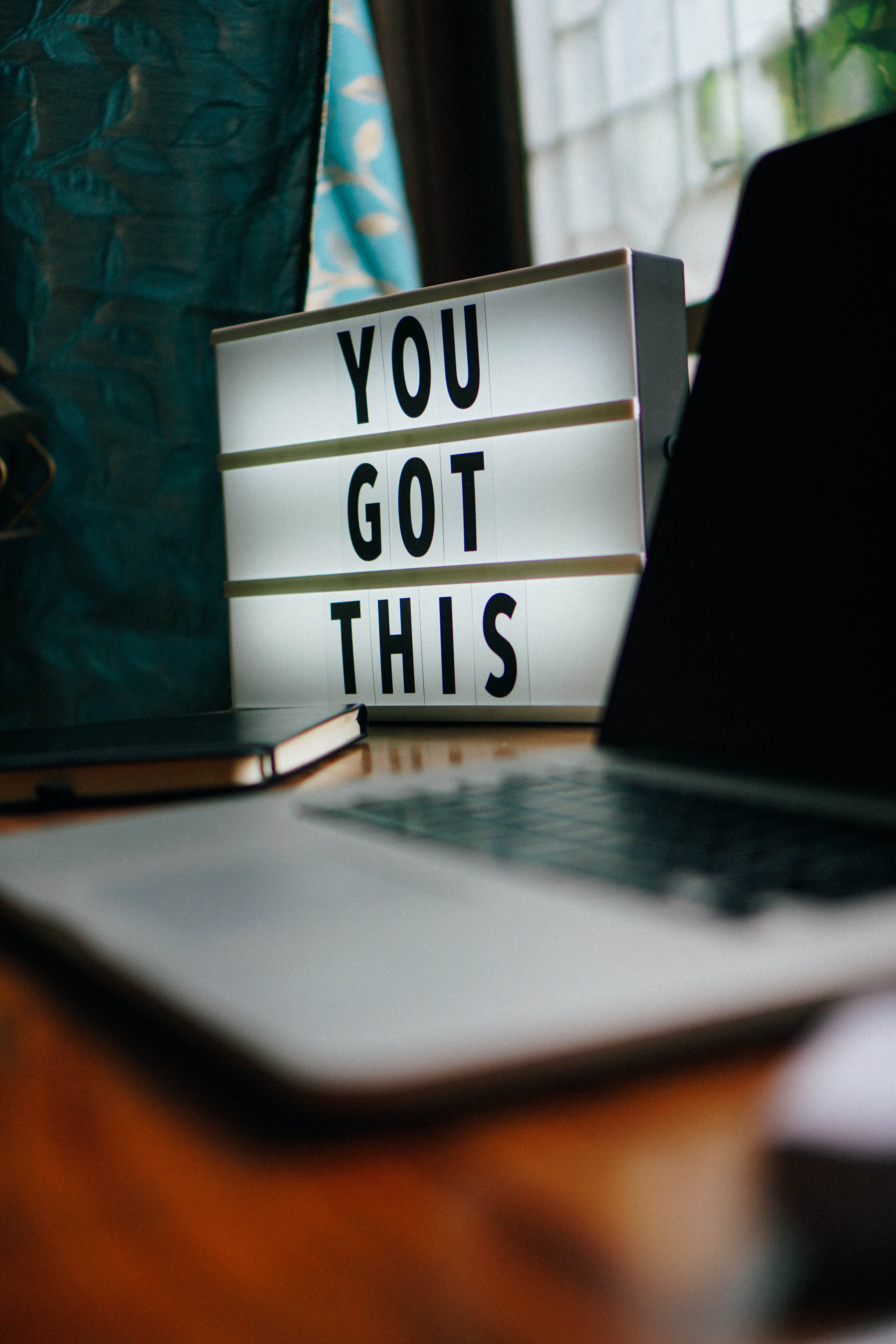 "a sign saying ""You Got This"" next to a lap top"