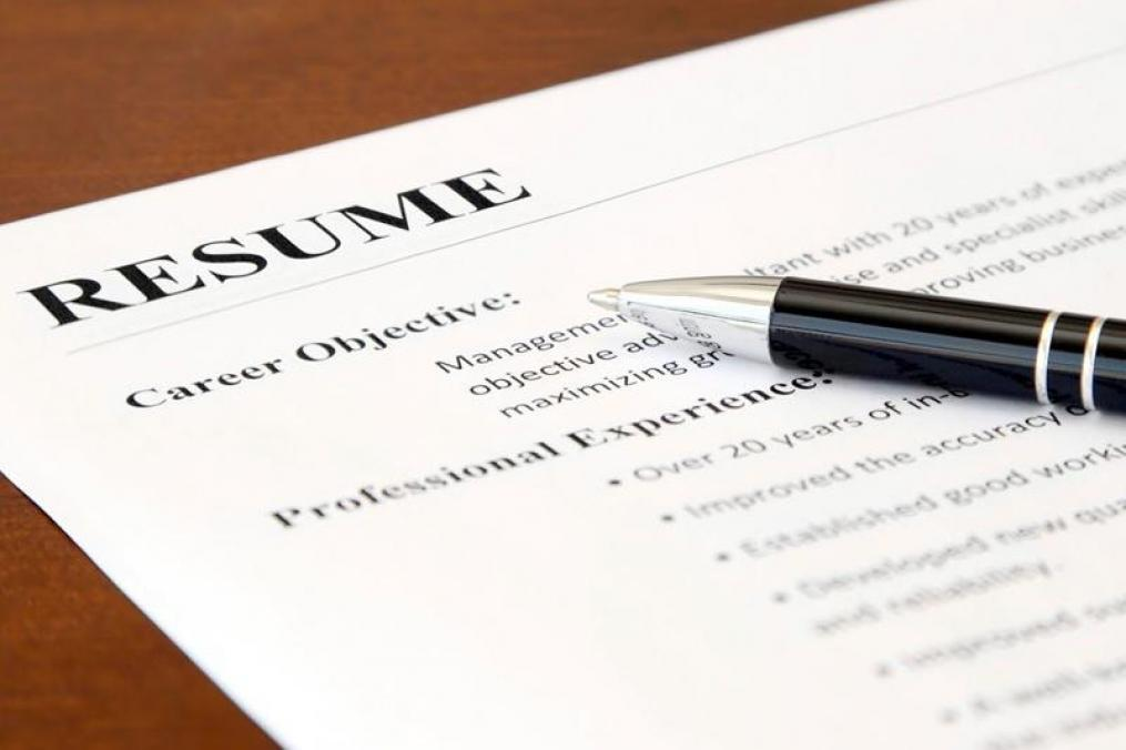 resume on a desk with a pen sitting on top of it