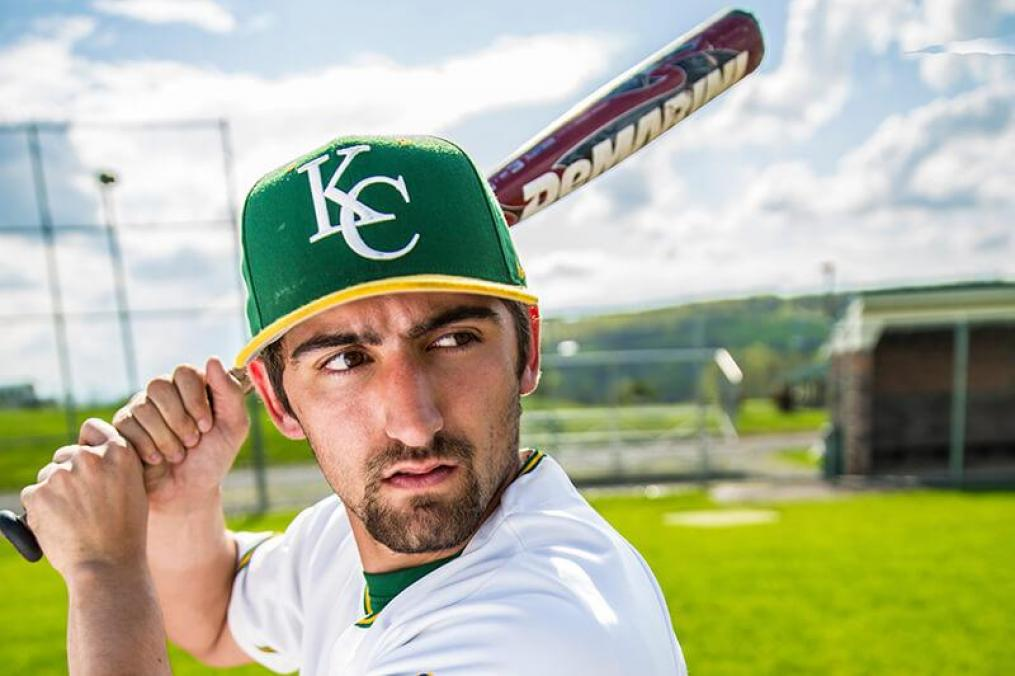 shoulders and above photo of a Keuka College athlete holding a baseball bat wearing a KC ball cap
