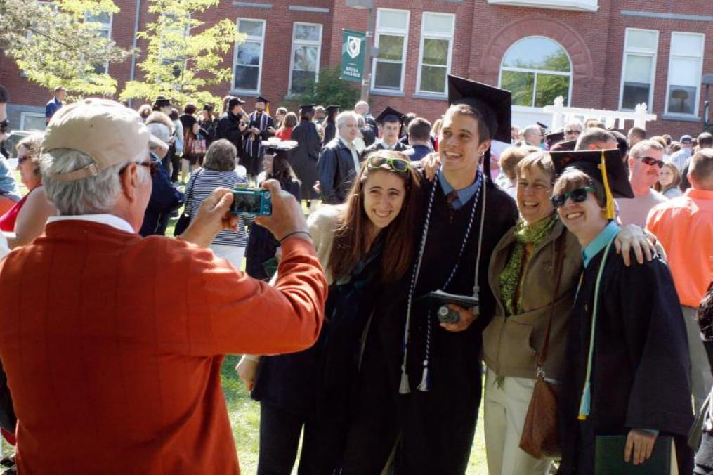 man taking a photo of two graduates in their cap and gown with two family members