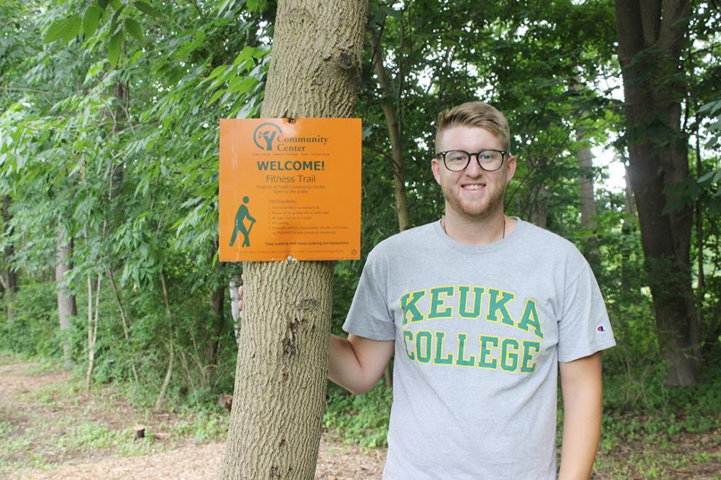 Senior Dan Lazzaro stands next to a sign marking