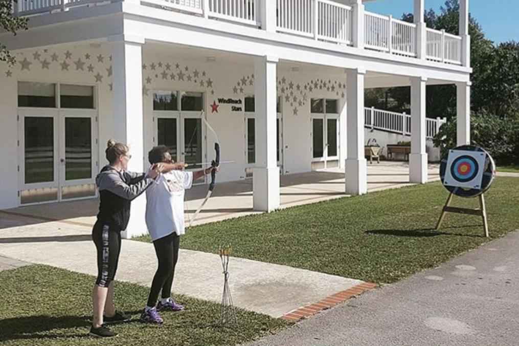Meg Calhoun '18 helps one of her students practice archery.