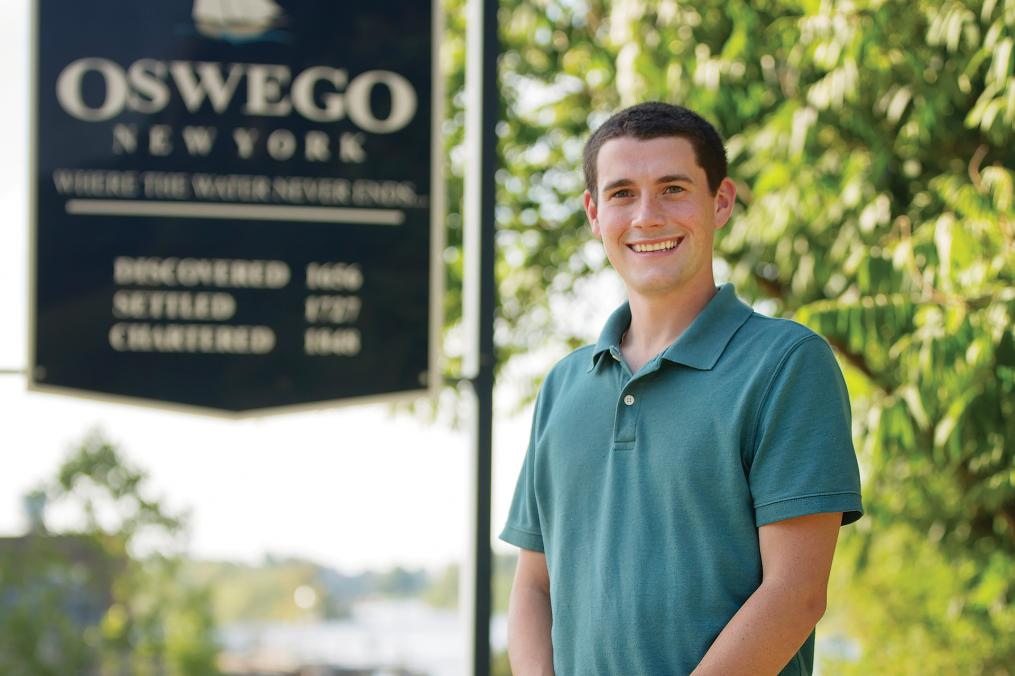 Tom Drumm '15 stands in front of an Oswego, New York sign. Tom represents Oswego in the County Legislature.