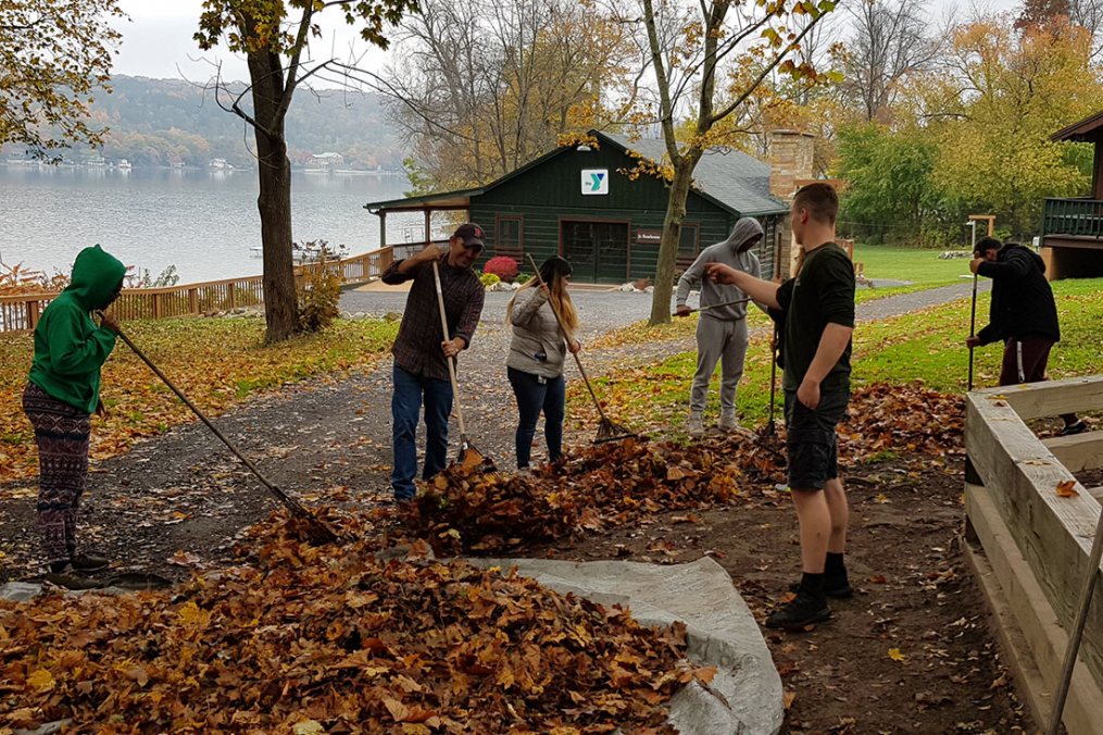 students raking leaves in a backyard with a lakeview