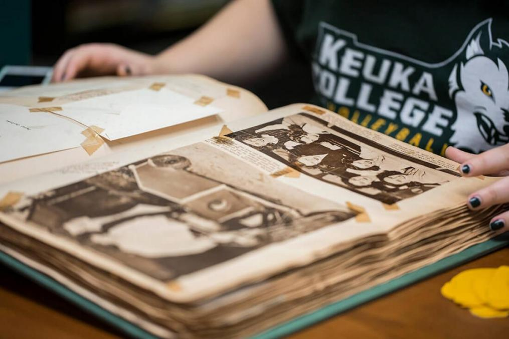 A student reads through a Keuka College history book