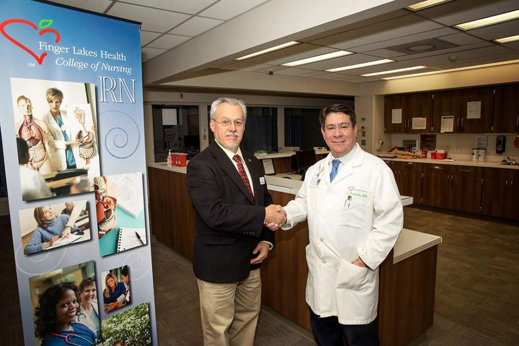 Keuka College President Jorge L. Díaz-Herrera, Ph.D., and Finger Lakes Health President & CEO Jose Acevedo, M.D., M.B.A. shake hands in the Finger Lakes Health College of Nursing laboratory.