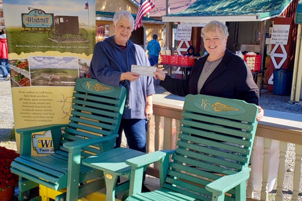 Mary Record, a longtime vendor at the Windmill and President of the organization's Board, presents a check from the Windmill to Kathy Waye, Keuka College's Director of Community Relations and Events.