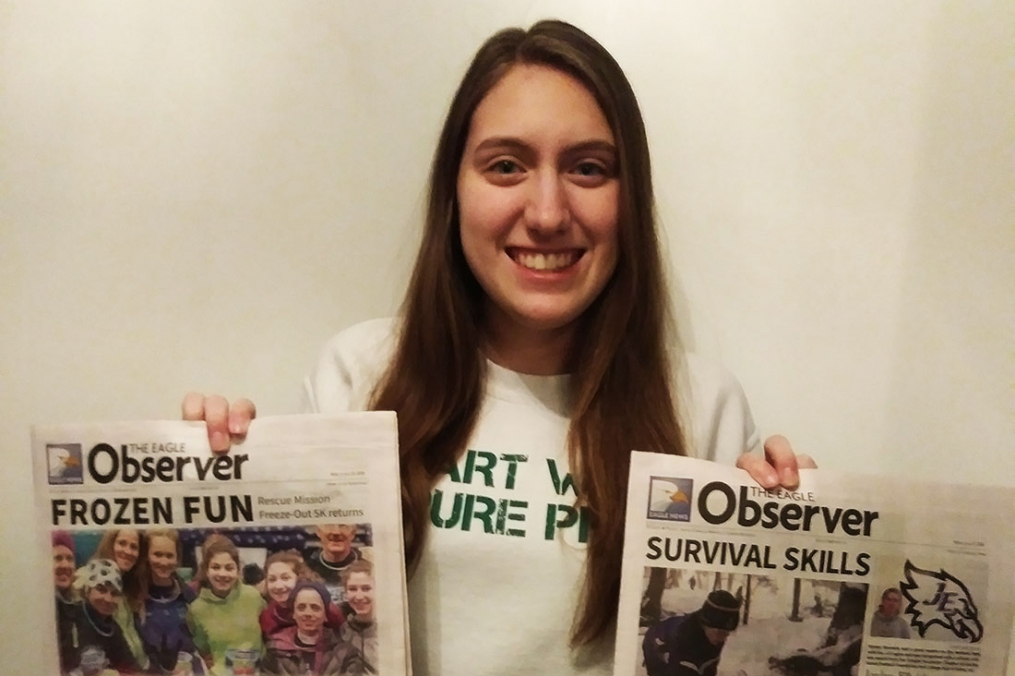 Christina Young holding two newspapers up showing off her headlines