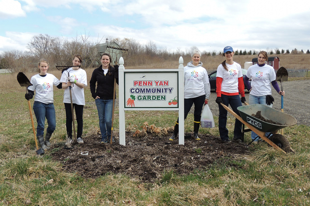 students posing by community garden sign