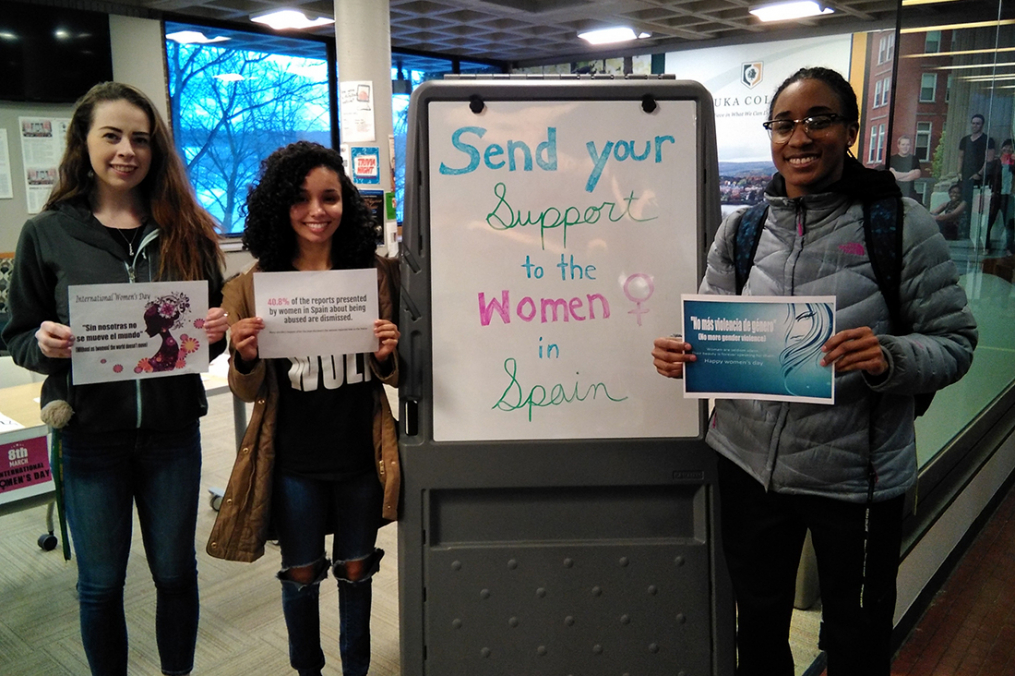"students standing by a sign saying ""send your support to the women in spain"""