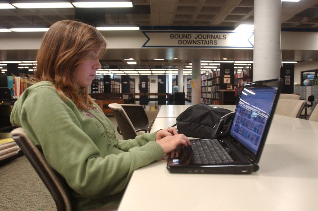 student on lap top in library