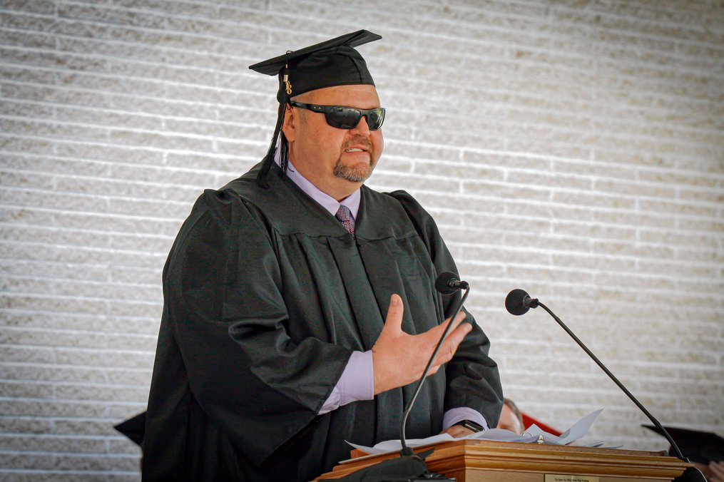 Guy in his cap and gown speaking at a podium at graduation
