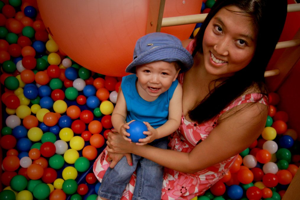 mom and child sitting in a container of colorful plastic balls