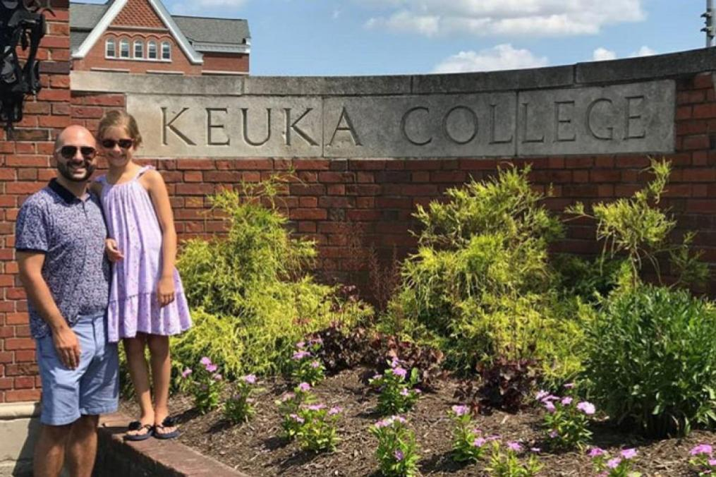 Dr. Brandon Barile '05 and his daughter, Sophia Barile-Swain, 8, stand by the front entrance of Keuka College.