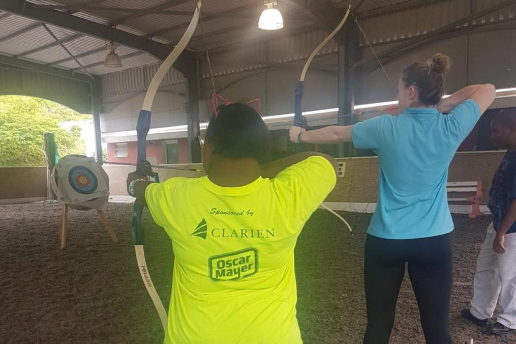 Meg Calhoun '18 (right) helps one of her students practice archery.