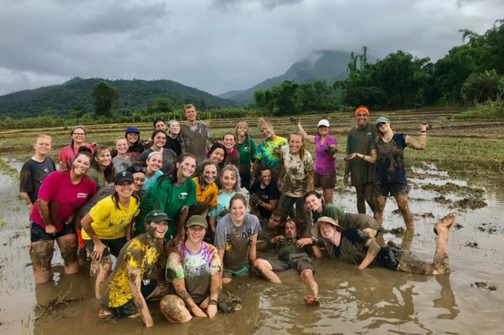 "Sarah Honan '21 completed a summer Field Period® in Thailand. Here, she poses with members of her Growth International Volunteer Excursions crew. ""Nothing compares to being barefoot, knee deep in a muddy rice paddy!"""