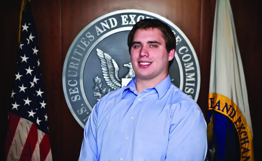 Dylan Campbell stands in front of the U.S. Securities and Exchange Commission seal.