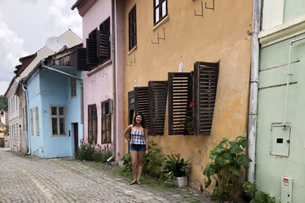 Ashley standing in front of houses and shops in Transylvania, Romania