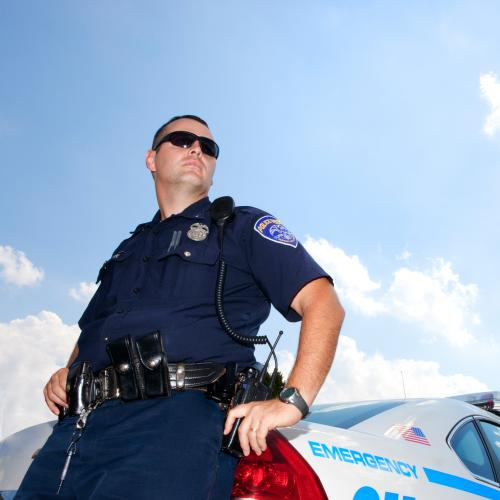 A police officer stands next to his car. Studies show that police officers with a Criminal Justice degree are happier in their positions.