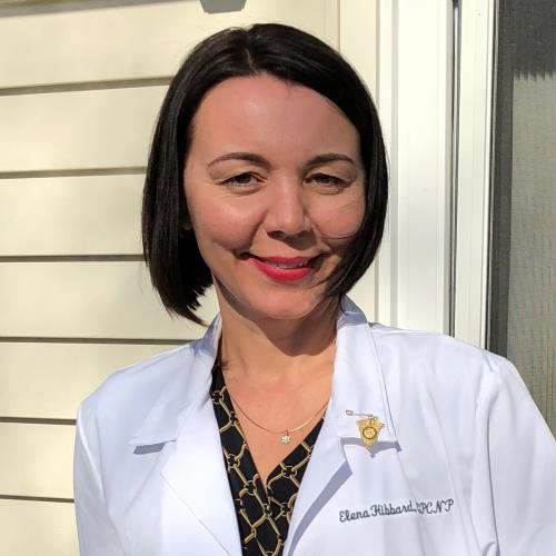 Elena Hibbard, an RN to BSN and NP graduate, outside her house wearing her lab coat.
