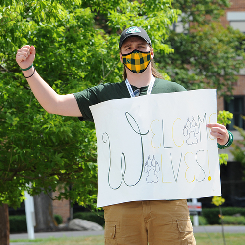 "student wearing a mask holding a ""welcome wolves"" sign"